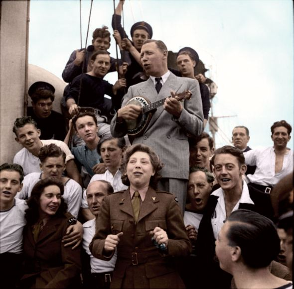 George Formby and his wife entertaining the crew of the Headquarters ship HMS AMBITIOUS, off the Normandy coast 1944