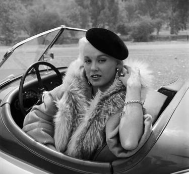 Mamie Van Doren sitting in her Jaguar 1954